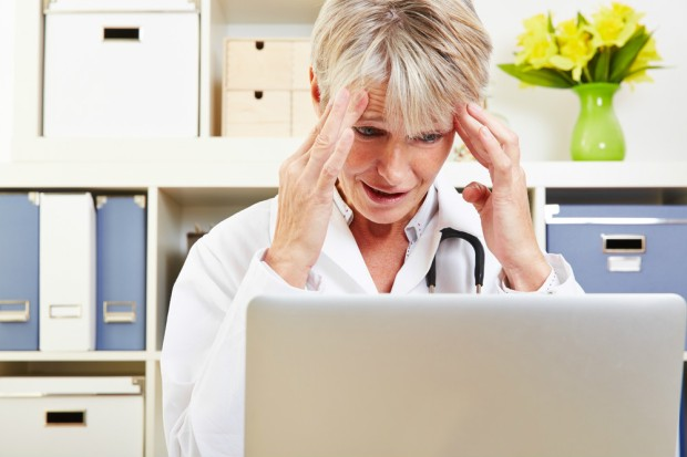Elderly woman doctor with burnout syndrome sitting at her desk (photo: shutterstock.com)