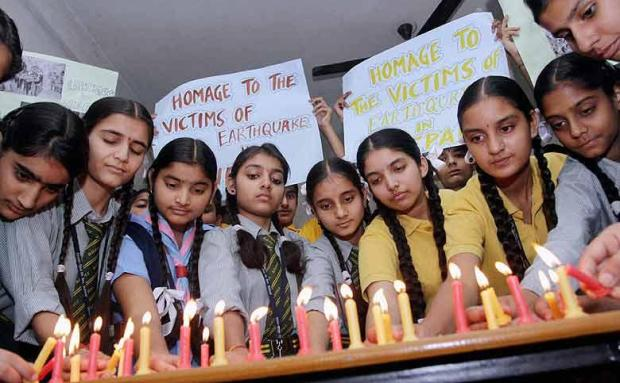 Students light candles as they pay tribute to the victims of the Nepal earthquake (photo via financialexpress.com)
