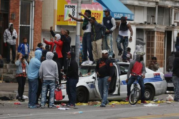 Demonstrators standing on top of a destroyed police vehicle during violent protests following the funeral of Freddie Gray April 27th 2015 (Getty Images)